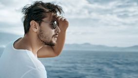 Portrait of a handsome man watching ocean waves. Portrait of a handsome guy watching ocean waves Royalty Free Stock Photo