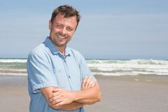 Handsome happy man model wearing blue clothes posing on beach sea background royalty free stock image