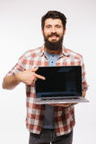 Portrait of handsome hipster bearded man with laptop. Bearded Man demonstrating laptop Royalty Free Stock Image