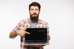 Portrait of handsome hipster bearded man with laptop. Bearded Man demonstrating laptop Royalty Free Stock Photo