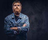 Portrait of a handsome hipster guy dressed in jeans jacket posing with crossed arms on a dark background. stock photography