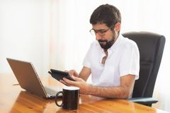Portrait of a handsome hipster guy working at the office royalty free stock image