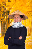 Portrait of a handsome hispanic young business guy wearing an asian conical hat with crossed arms in autum background Royalty Free Stock Photography