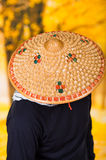 Portrait of a handsome hispanic young business guy wearing an asian conical hat and hiding his face with the hat, in Stock Photos