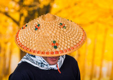 Portrait of a handsome hispanic young business guy wearing an asian conical hat and hiding his face with the hat, in Royalty Free Stock Image