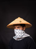 Portrait of a handsome hispanic young business guy wearing an asian conical hat and hiding his face with a scarf in Stock Image