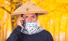 Portrait of a handsome hispanic young business guy wearing an asian conical hat, hiding his face with a scarf and using Royalty Free Stock Photos