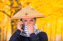 Portrait of a handsome hispanic young business guy wearing an asian conical hat, hiding his face with a scarf and using Royalty Free Stock Photography
