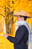 Portrait of a handsome hispanic young business guy wearing an asian conical hat and a scarf around his neck holding his Stock Image