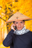 Portrait of a handsome hispanic young business guy wearing an asian conical hat and a scarf around his neck using his Royalty Free Stock Images