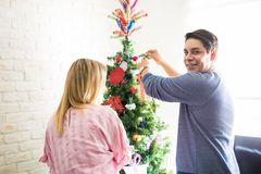 Decorating Christmas tree with his girlfriend. Portrait of a handsome Hispanic young men putting on some Christmas decorations on a tree with his girlfriend stock image
