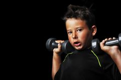 Portrait of handsome kid doing exercise with dumbbells Stock Image