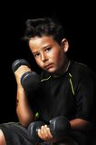 Portrait of handsome kid doing exercise with dumbbells Stock Photos