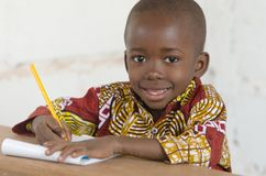Portrait of handsome little African Black Boy Learning to Write. Candid shot of black African children outdoors in Bamako, Mali. By buying this image you Royalty Free Stock Photos