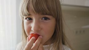 Portrait of a handsome little girl in white dress that eats tasty ripe tomatoes in the kitchen. Close-up. Cute kid stock video