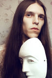 Portrait of handsome long-haired poet with a white mask Royalty Free Stock Photo