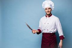 Portrait of a handsome male chef cook holding knifes isolated on light blue background. Portrait of a handsome male chef cook holding knifes isolated on light stock photos