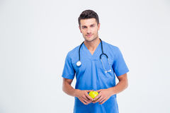 Portrait of a handsome male doctor holding apple. Isolated on a white background and looking at camera Stock Photo