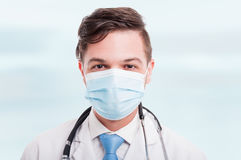 Portrait of handsome male doctor with mask. And white coat being ready for consultation Stock Photo