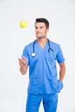 Portrait of a handsome male doctor standing with apple. Isolated on a white background Stock Images