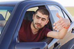 Portrait of handsome male driver waves from car window, being stuck in traffic jam, feels nervous and worried, looks into distance. Notices accident on road Royalty Free Stock Images