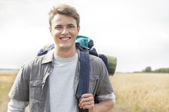 Portrait of handsome male hiker with backpack standing on field Royalty Free Stock Photography