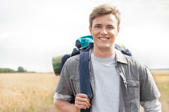 Portrait of handsome male hiker with backpack standing on field Royalty Free Stock Images