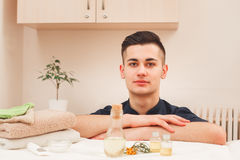 Portrait of handsome male masseur in black apron. Young smiling male professional massagist posing at workplace near aroma therapy set, looking at camera Stock Photos