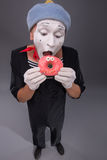 Portrait of handsome male mime eating a tasty pink Stock Images