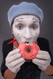 Portrait of handsome male mime eating a tasty pink Royalty Free Stock Photography