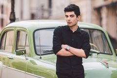 Portrait, handsome, male, model, brunette Mediterranean race Turkish man stands near a retro car of green color posing royalty free stock image