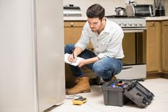 Male technician writing a work report. Portrait of a handsome male technician doing a work report on a broken fridge in a home kitchen Royalty Free Stock Photos