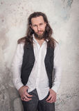 Portrait of handsome man with beard and long hair. On wall background Stock Photography