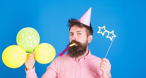 Portrait of handsome man with beard, wearing pink shirt and party hat, whistling in party horn, holding colorful. Balloons, looking into camera. People royalty free stock photography