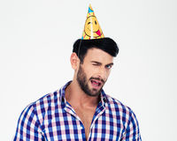Portrait of a handsome man in birthday hat winking Stock Photo