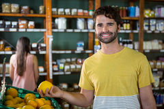 Portrait of handsome man buying sweet lime in organic section Stock Photos