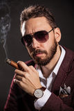 Portrait of handsome man in casual dress smoking a cigar Royalty Free Stock Photo