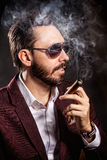 Portrait of handsome man in casual dress smoking a cigar Royalty Free Stock Images