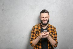 Portrait of handsome man with cell phone. On grey background Royalty Free Stock Photos
