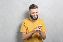 Portrait of handsome man with cell phone. On grey background Stock Photography