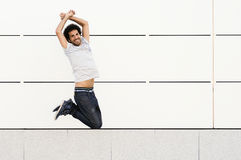 Man with curly hairstyle jumping in urban background Royalty Free Stock Images