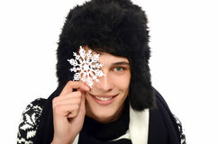 Portrait of a handsome man dressed for a cold winter holding up a big snowflake. Royalty Free Stock Photos