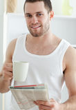 Portrait of a handsome man drinking coffee while reading the new Royalty Free Stock Photo