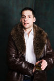 Portrait of handsome man in fur coat with glass of whiskey Stock Image