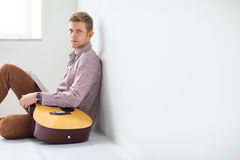 Portrait of handsome man with guitar siting on floor Stock Photo