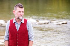 Portrait of man in his 50s standing by the river Royalty Free Stock Image