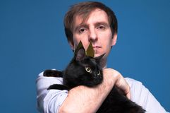 Portrait of handsome man holding cute black cat in golden crown royalty free stock images