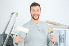Portrait handsome man holding paint roller in new house. Portrait of handsome man holding paint roller in new house stock photography