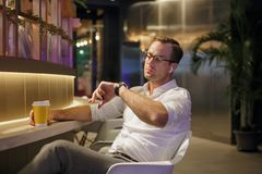 Portrait of a handsome man in the interior with coffee and earphones stock photography