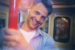 Portrait of handsome man listening music. In train Stock Photo